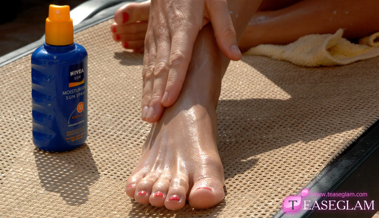 Holly Newbury sprays her feet with sun cream